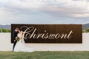 bride-and-groom-at-driveway-entrance-of-chrismont